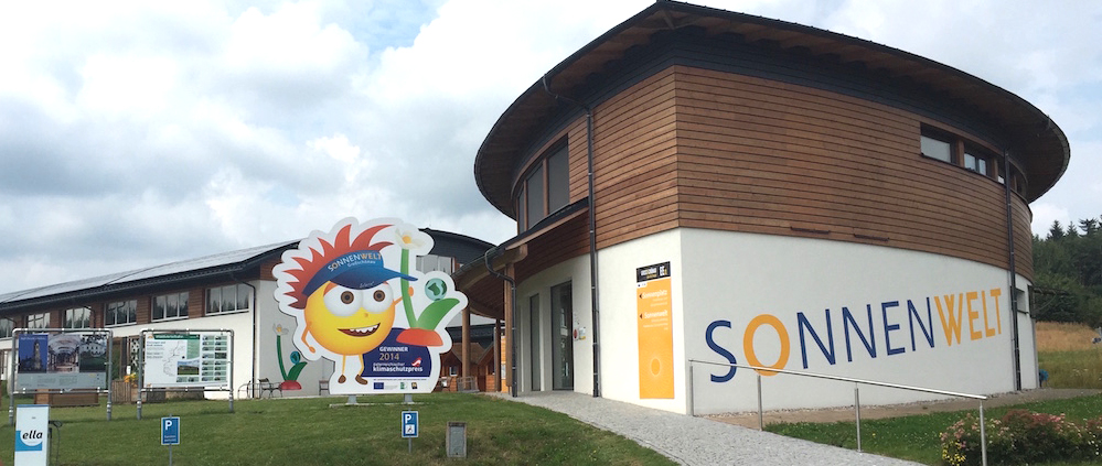 Dieses Bild zeigt das Gebäuder der Sonnenwelt von Aussen mit dem Maskottchen namens Solarix.