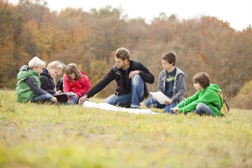Kinder und Ranger mit Karte und Kompass bei Schulprogramm Überleben in der Wildnis